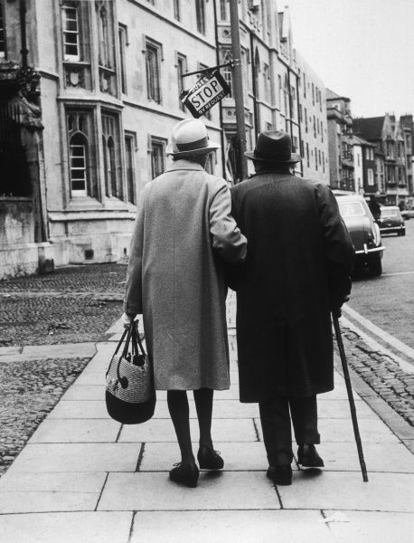 An elderly couple walking down the street, arm in arm