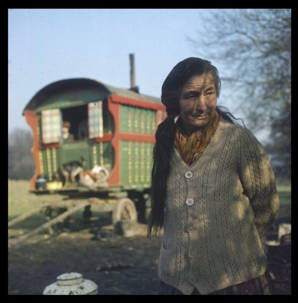 An elderly gypsy woman with long dark hair and wearing a thick cardigan stands in front of the brightly painted family caravan at an encampment in Surrey