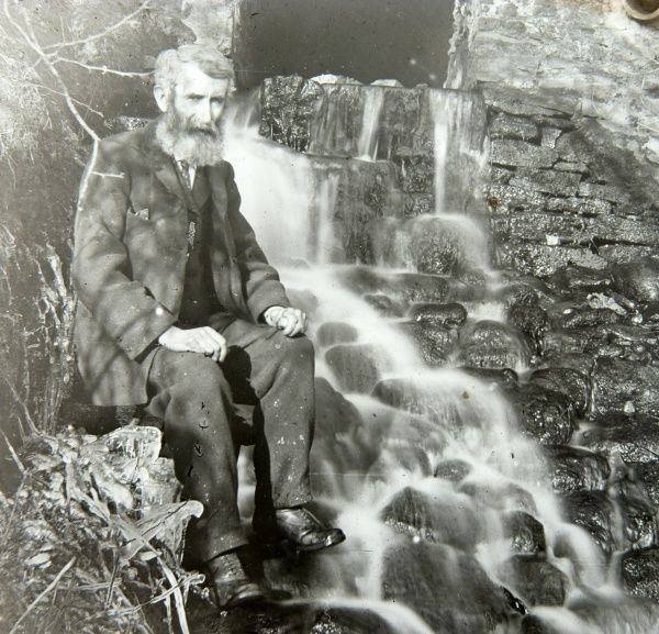 An elderly man sitting by the outflow of a mill, on a sunny day