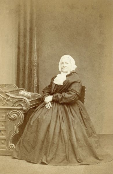An elderly Victorian woman in a dark crinoline dress sitting at the side of an ornate desk in the photographer's studio. She wears a white bonnet and is looking rather severe