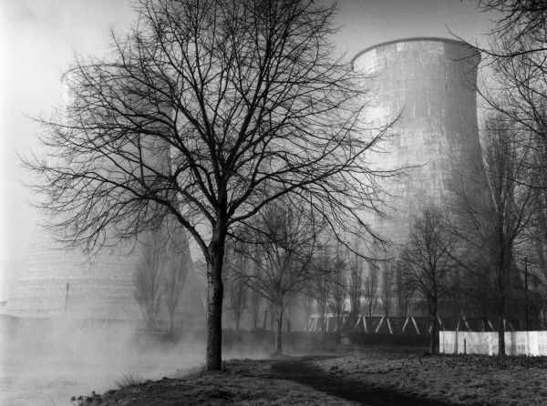 Winter study of the electricity cooling towers at Northampton, Northamptonshire, England, in the morning sunshine, with mist rising from the River Nene. Date: 1960s