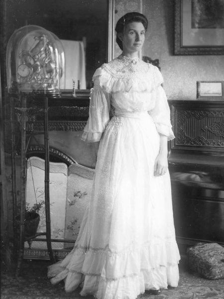 An elegant lady in a full-length white dress poses in a country house interior in Mid Wales. There is a fireplace and decorated screen on the left, and an upright piano on the right