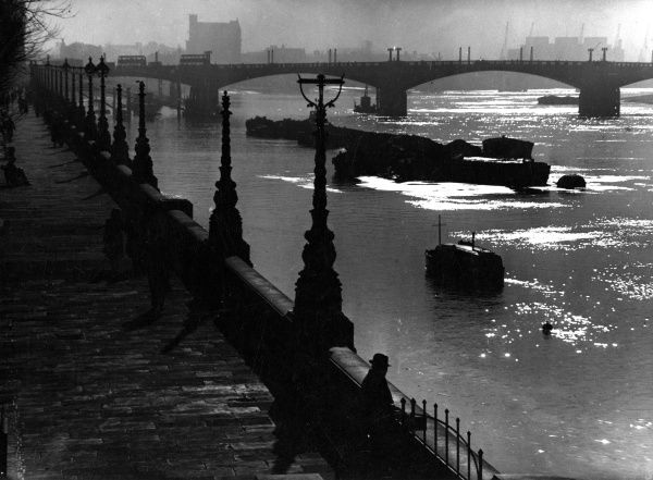 View of the Embankment and River Thames, London, on a misty day, with traffic crossing a bridge.  circa 1940s