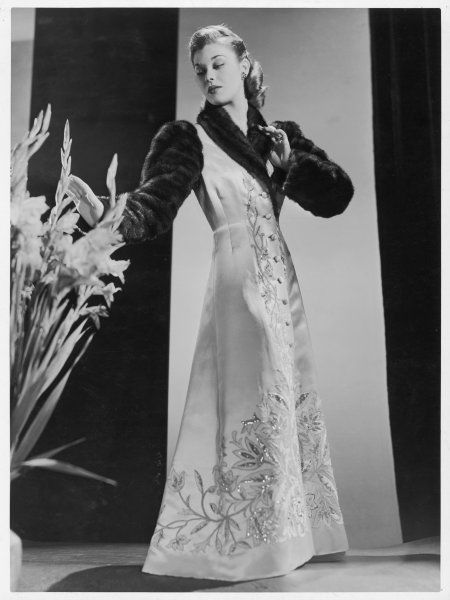 A design by Raphael: A full length evening coat in white satin profusely embroidered with sequins & with a fur roll collar & sleeves