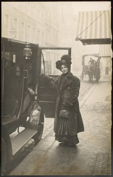 EMMELINE PANKHURST standing by a motor car. (There are stickers on the back of this postcard advertising the meeting 18 Nov 1910 which came to be known as Black Friday)