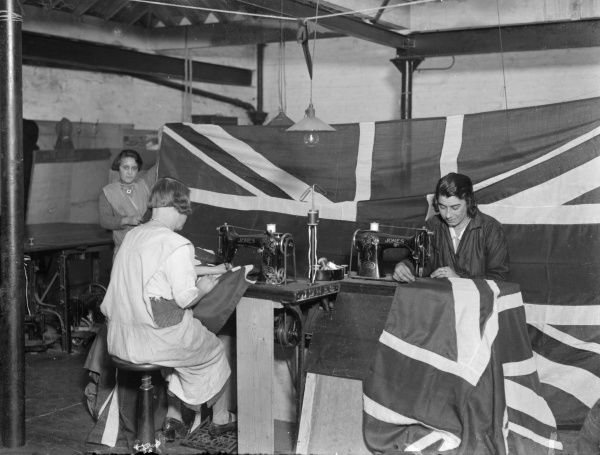 British women making Union Jack flags for Empire Day, when the British Empire was celebrated in Britain and the Commonwealth. Date: early 1930s