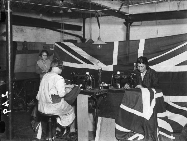 Women at sewing machines making Union Jack flags for Empire Day, (May 24, Queen Victoria's birthday), which was celebrated between 1904 and 1958