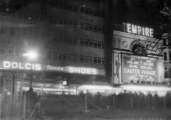 The Empire cinema, Leicester Square, London, showing Easter Parade starring Judy Garland and Fred Astaire. Next door is a large Dolcis fashion shoes sign. Date: 1948