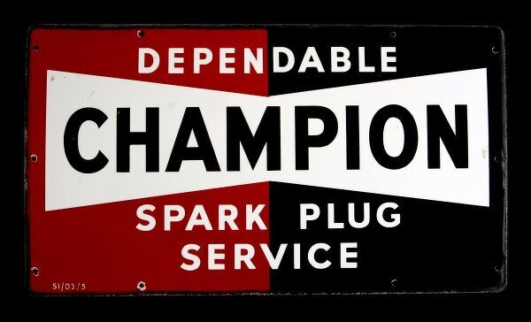 An enamel sign advertising the Champion Spark Plug Service. *EDITORIAL USE ONLY*