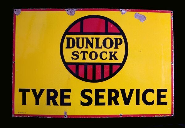 An enamel sign advertising Dunlop Stock Tyre Service. *EDITORIAL USE ONLY*