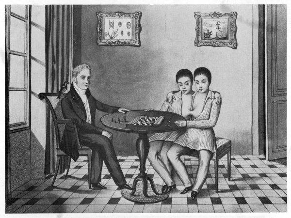 Eng and Chang, Siamese twins, aged about 12, sitting at a table with a visitor, playing a board game