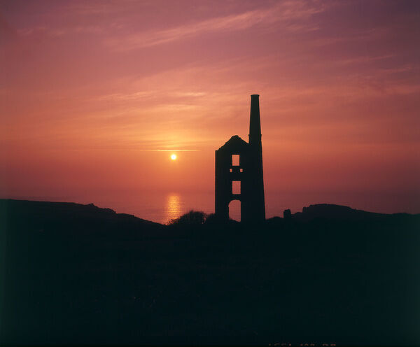 Engine house silhouetted against the sky at sunset at Carn Galver disused tin mine, near Bosigran, Cornwall. Date: 20th century