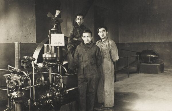 Three Turkish engineers stand proudly in front of a large piece of belt-driven machinery, possibly a generator