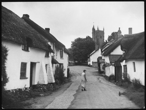 A girl and her dog walk through the idyllic village of Broadhembury, Devon, with its typical thatched cottages and village church