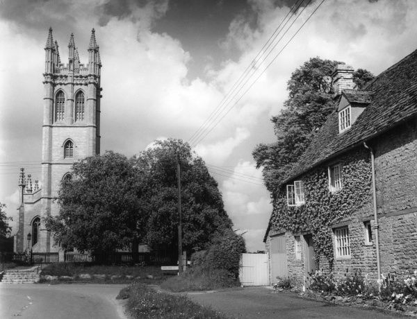 A picturesque corner in the village of Churchill, Oxfordshire, England, with the tall and graceful tower of All Saints Church. Date: early 1960s