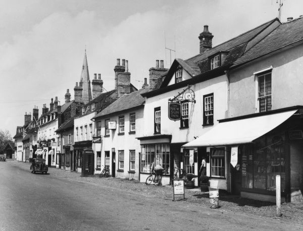 The pleasant village of Kimbolton, Cambridgeshire, England, with its wide main street and charming old white- fronted shops