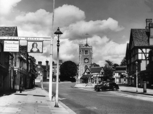 The charming centre of Pinner, Greater London, England. showing the pub sign of the 'Queen's Head' on the left and the church in the background. Date: 1950s