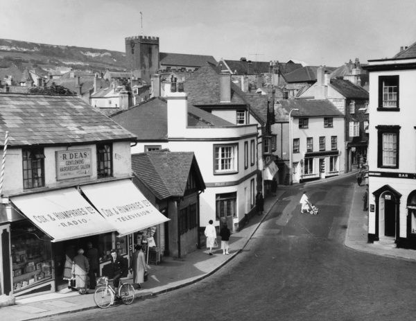 A glimpse of Lyme Regis High Street, Dorset, England, showing a young man on a bicycle outside 'Cox & Humphries' radio shop and the church in the background