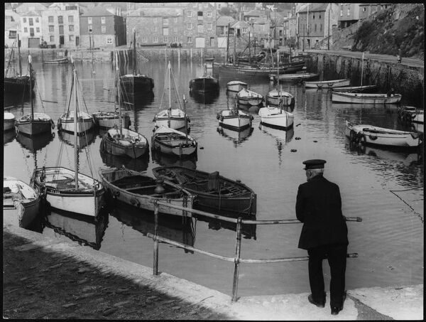 A quiet and placid scene, by the old harbour, where an old Cornish fisherman takes in the scene in the village of Mevagissey, Cornwall, England