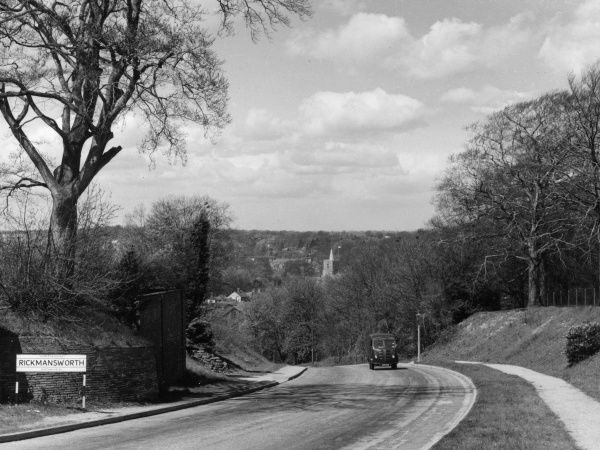 A solitary vehicle leaving Rickmansworth, Hertfordshire, England, in the days when it was more like a country lane. Date: 1950s