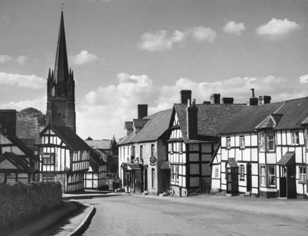 Weobley, a beautiful Herefordshire market town of old half-timbered houses, mellowed by age and clustering round an imposing 14th century church. Date: 1950s
