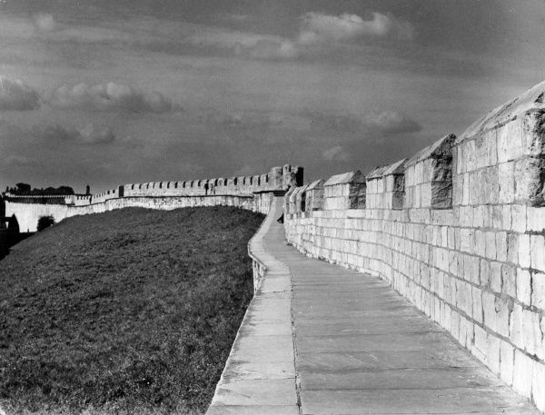 The fine old city walls of York, which date from the reign of King Edward III. In the distance can be seen the famous York Minster, England. Date: 1940s