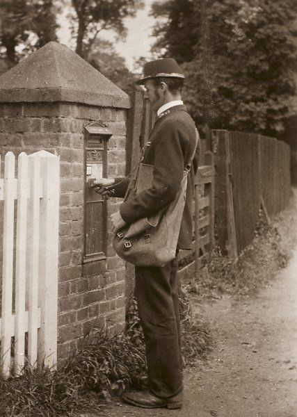 An English rural postman collects the mail from a letter-box