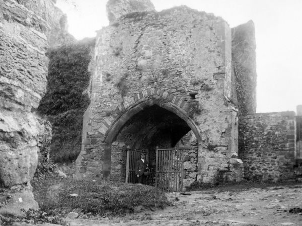 The wide gothic-style entrance to the medieval Bishop's Palace, with a man standing at the open gate, in St David's, Pembrokeshire, Dyfed, South Wales
