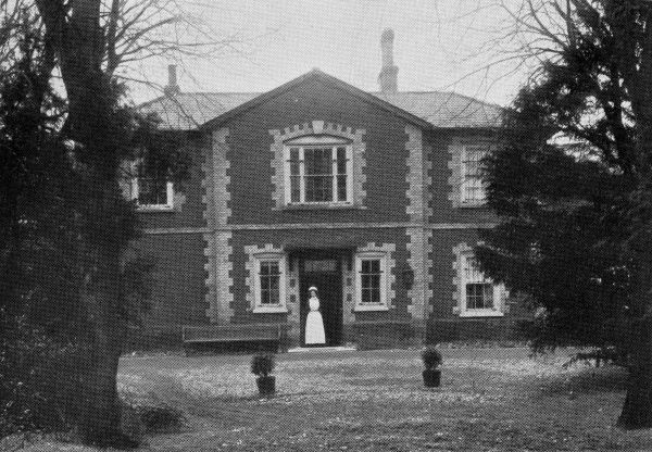 A woman in nurse's uniform at the front entrance of the East Harling, Norfolk, branch of the National Institutions for Persons Requiring Care and Control, an organisation privately run by the Rev Harold Burden to house 'feeble minded' children