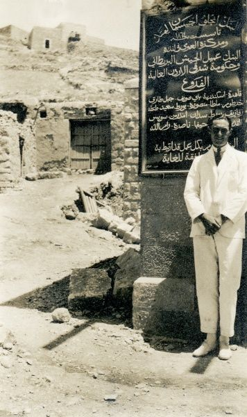 A European man in a dazzling white suit with rather short trousers and white shoes poses in front of a handwritten sign in arabic writing, in a street somewhere in the Middle East