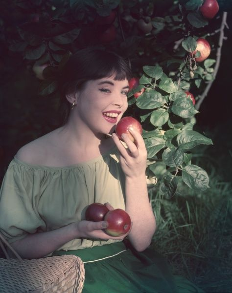 A pretty brunette model re- enacts a scene from the Garden of Eden. She smiles wickedly as she raises a ripe red apple to her lips