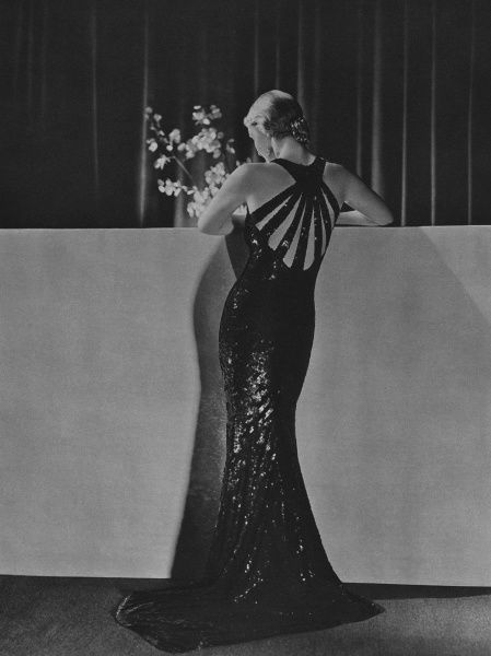 An evening dress by Patrick Perrott, designed for Liberty, composed of sequins made from the shavings of tortoiseshell combs with rayed straps at the back giving it an 'enviable distinction'. Date: 1934