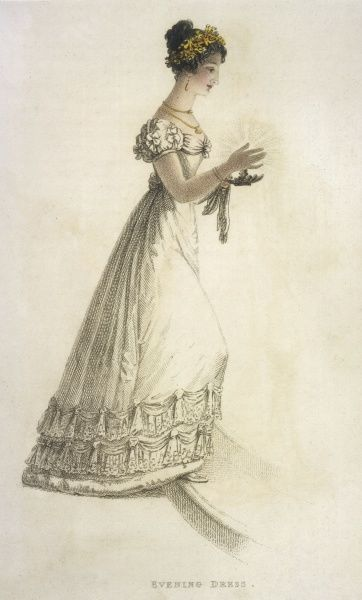 A bewitching young lady in white holds a candle to illuminate her path. The hemline is wadded & decorated with 2 rows of lace. Her headdress is gold & red