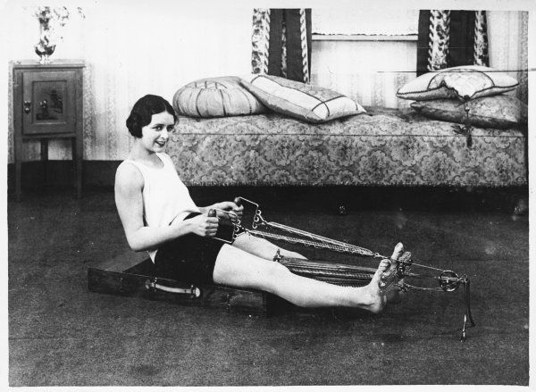 This wise young woman is toning up and slimming down with the aid of a new fangled rowing exercise machine!