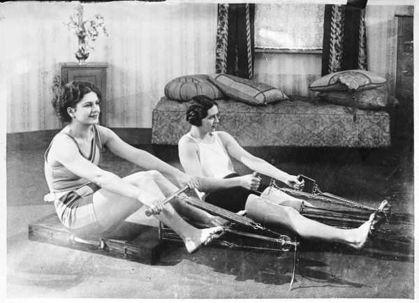 Two young women, toning up and staying slim with the aid of their new fangled rowing exercise machines!