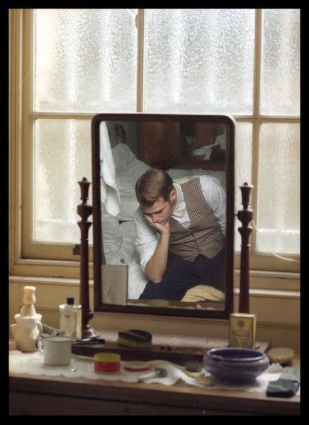 An exhausted footman, reflected in a dressing table mirror, rests his weary head in his hands and ruminates on the lot of an Edwardian servant
