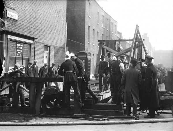 Firemen deal with an explosion in Medway Street, Victoria, London. An interested crowd gathers to watch their progress