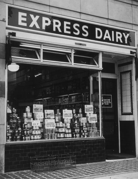 The shop front of an Express Dairy which has a range of food such as McVities digestive biscuits, processed peas and sliced peaches