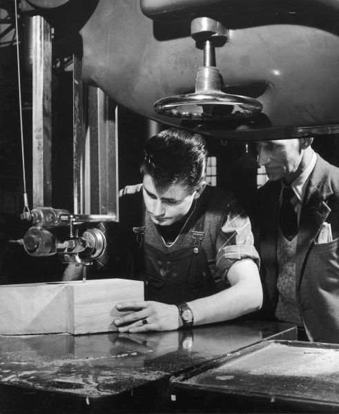 A young apprentice carpenter uses a large industrial jigsaw to cut a block of wood, while an older employee supervises his work. Photograph by Heinz Zinram