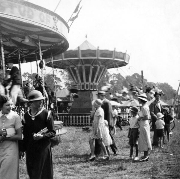 A busy scene at a fairground, showing families milling around the rides, most of them wearing various types of hats - cloche, pith helmets, straw boaters, trilbys, etc. Date: early 1930s