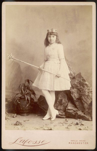 A girl in a fairy costume. Her short, white dress has sequinned sleeves & belt. Also: white stockings & court shoes with roses, a crown, wand & fingerless mittens