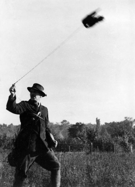The falconer lets the bird fly, but holds it securely on a leash. Date: 1930s