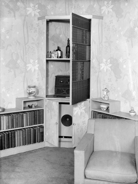 A false corner cupboard bookcase, concealing a drinks shelf, radio and speakers! Date: early 1930s