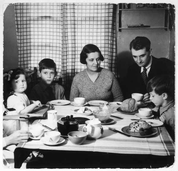 A family sit round a table and take afternoon tea. Date: 1930s