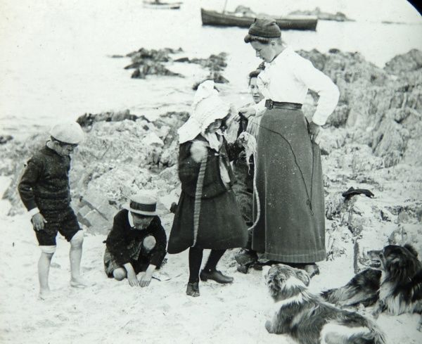 An Edwardian family with their two dogs at the beach in Pembrokeshire, Dyfed, South Wales. The sea is visible in the background, with two boats