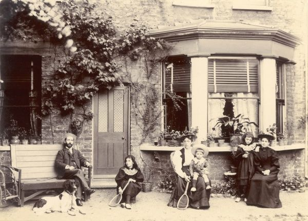 A family break off from their tennis game to be photographed informally in their garden, with their dog, probably in Sussex, England