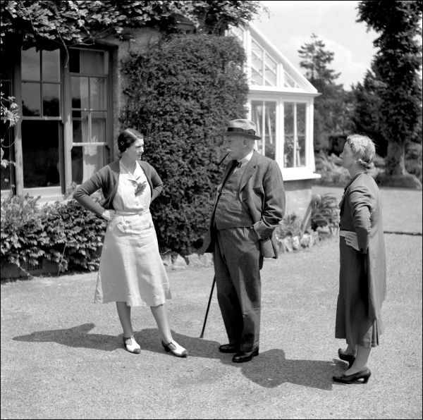 A family group chatting in a Devon garden -- from left to right Olive Harper, Edwin Pitts Tucker, and Christine Watts