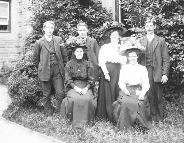 A family group of six -- three men and three women -- in a garden in Mid Wales. All the women are wearing very large hats