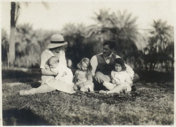 A family group of five -- mother, father and three children -- sitting on the grass with palm trees in the background, somewhere in the Middle East