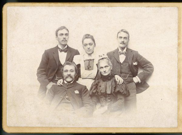 A family of five: the three men seem amused by something, but the two women look serious